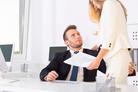 Woman giving businessman documents while he is grabbing her buttocks Stock Photo