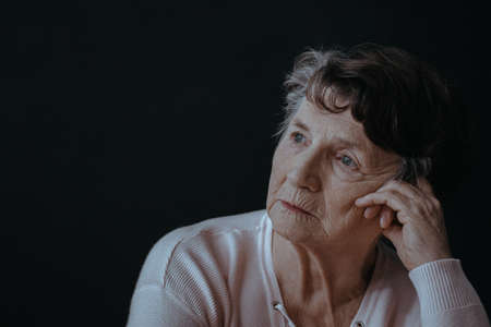 Portrait of worried, senior woman, black background Stock fotó