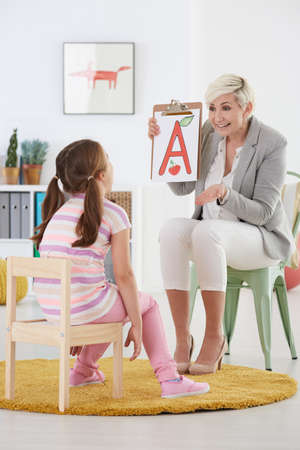 Female speech therapist teaching young girl the alphabet
