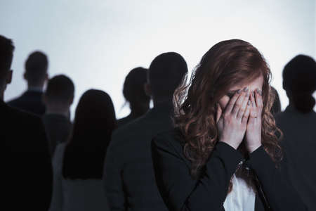 Young woman covering her face and crying standing back to back with a crowd Stock Photo