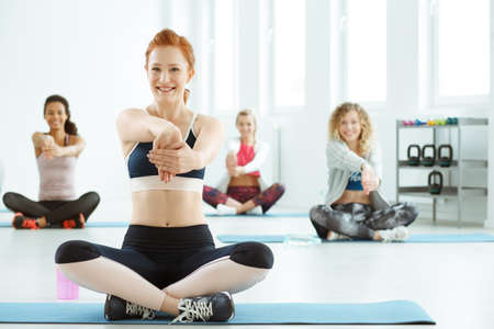 Group of fit women stretching arms after fitness classes