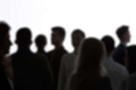Anonymous blurred crowd of people standing against white background
