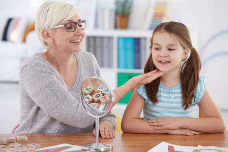 Speech therapist touching girl's chin during articulate therapy Reklamní fotografie - 78563362