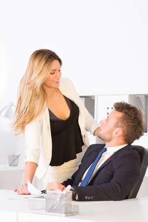 Businesswoman flirting with her work colleague in dark suit Stock Photo