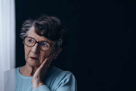 Sad, old woman standing alone in dark room