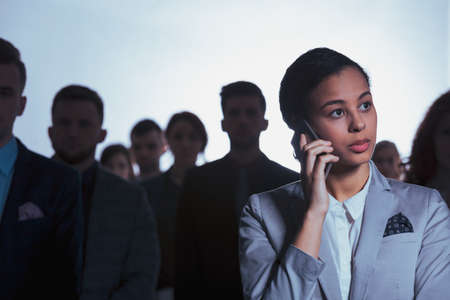 Young serious businesswoman talking on a phone in crowd of blurry people