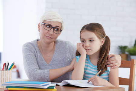 Woman encouraging young girl to concentrate on her homework