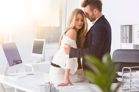 Man slowly undressing businesswoman on desk at work