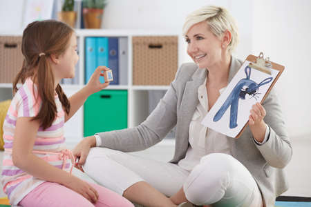 Girl learning alphabet with her female speech pathologist Stock Photo - 78110545
