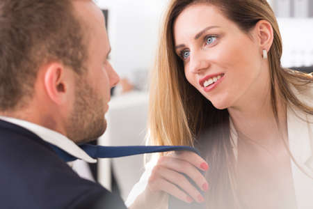 Attractive female boss harassing co-worker by grabbing his tie