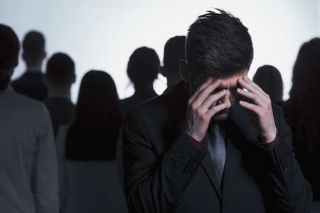 Overwhelmed man in a suit standing against a crowd of people Stock Photo