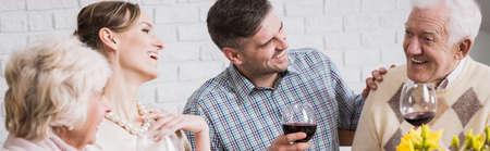 Panoramische foto van een familiebijeenkomst aan de tafel, drinken van wijn en lachen