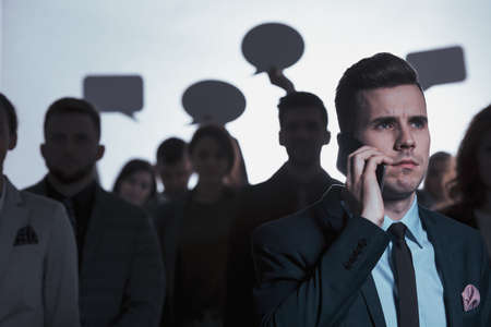 Serious man calling and standing against a crowd holding speech bubbles Imagens