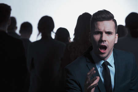 Young businessman screaming while standing against crowd of people