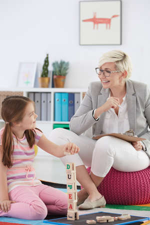 Educational psychologist and young girl during therapy session Stock Photo - 78110831