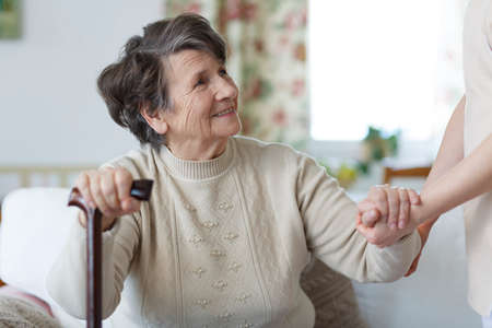 Smiling senior woman holding a cane and looking at her caregiver Stockfoto