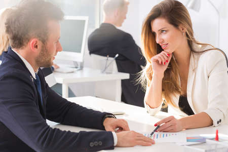 Woman looking teasingly at her colleague while working in the office