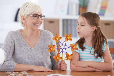 Girl interested in paper windmill held by smiling woman