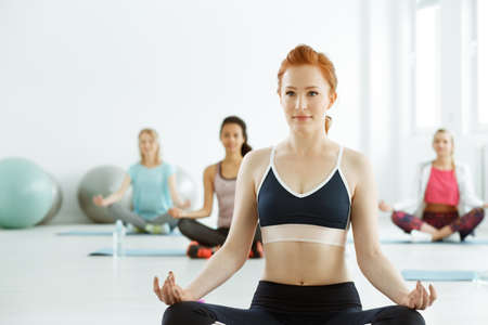 Young pretty fit woman meditating on yoga classes