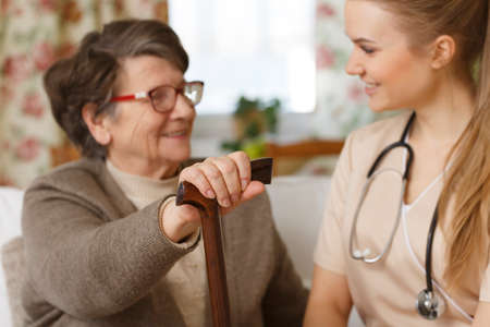 Smiling grandma holding a cane and talking with a young nurse