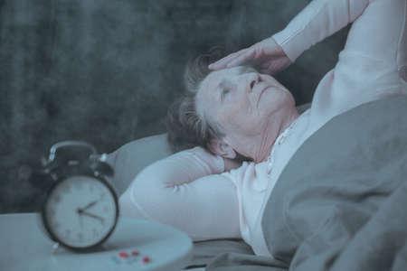 침대에서 자고있는 수면 장애가있는 노인 여성