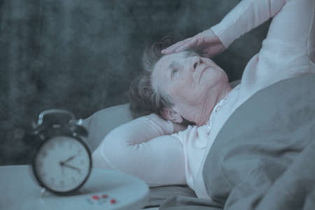 Senior woman having sleep disorder, lying in bed
