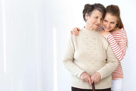 Gelukkige kleindochter die zich achter haar oma bevindt en haar koestert
