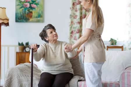 Young nurse helping sad elderly woman to stand up from the sofa Stock Photo