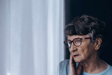 Sad, lonely senior woman suffering from depression Фото со стока