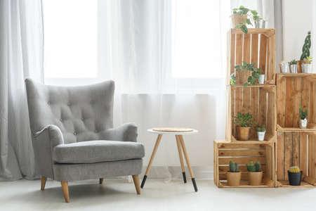 灰色の肘掛け椅子の横にある木箱で作られたモダンな棚