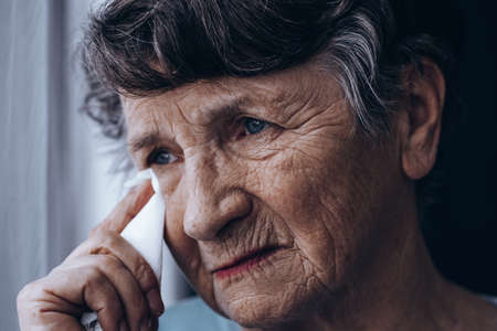 Portrait of crying senior woman, holding tissue Stock Photo - 78146623