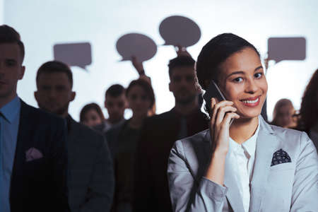 Smiling young businesswoman calling while standing in a crowd