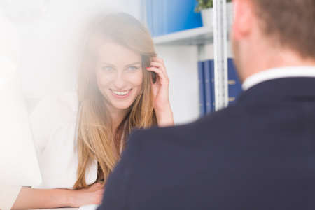 Seductively smiling woman touching hair during a conversation with boss
