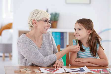 Smiling woman looking at young girl learnig to articulate Stock Photo