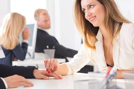 sexualidad: Mujer oficinista coqueto tocando su mano de compañeros de trabajo