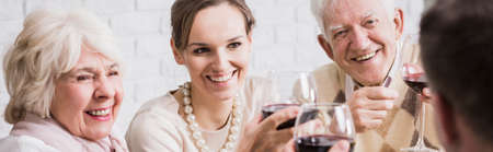 Close-up of elegant family members sitting at the table, laughing and drinking wine