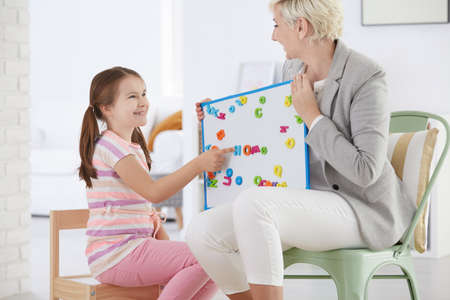 Woman holding whiteboard with girl learning alphabet with magnet letters