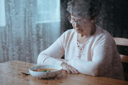 Sad, senior woman having lack of appetite Stock Photo