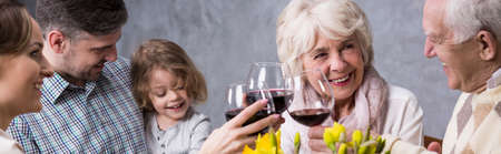 anecdote: Panoramic photo of a whole family sitting at the table together, talking cheerfully and drinking wine Stock Photo