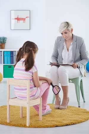 Girl talking with her therapist in therapy center interior Stock Photo