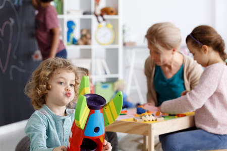 Preschool boy playing with colorful toy rocket