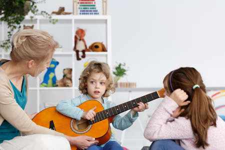 Little preschool boy learning how to play the guitar Stock Photo