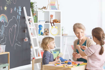 Preschool children in kindergarten sticking with plasticine on classes