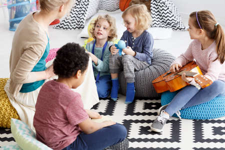 Group of preschool kids sitting on a carpet in kindergarten