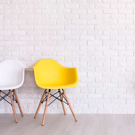 living room design: White and yellow chair standing in white room with brick wall