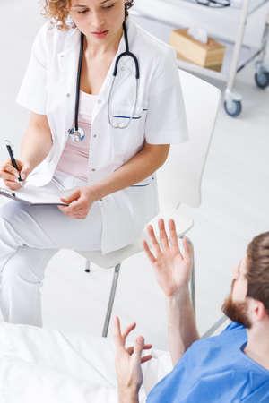 明るい病棟の麻痺患者と話している精神科看護師