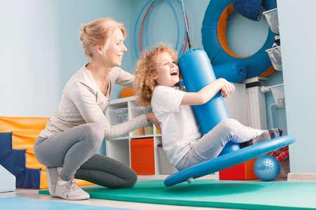 Kind dat evenwichtsoefeningen op therapeutische schommeling doet