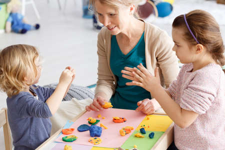 Two little girls and teacher plying with plasticine on classes