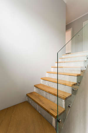 Concrete and wooden stairs with glass balustrade in modern minimalist interior