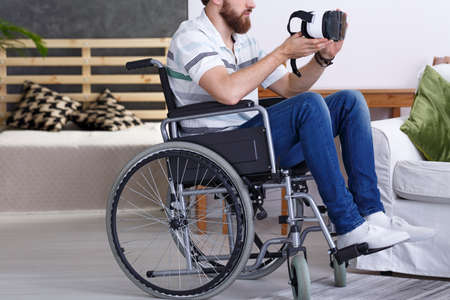 stress testing: Young man sitting on wheelchair and using VR glasses Stock Photo
